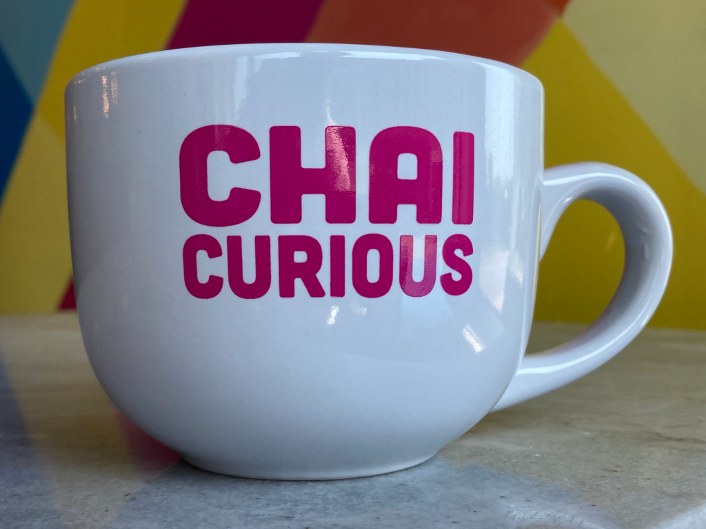White mug with pink font - chai curious